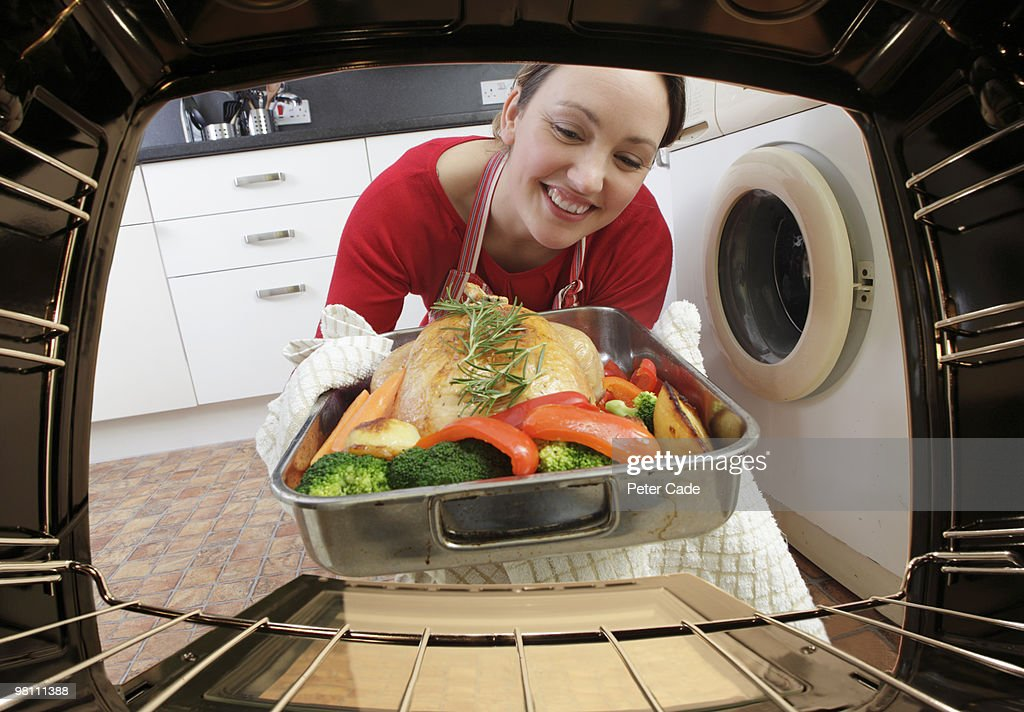 Putting chicken in oven : Stock Photo