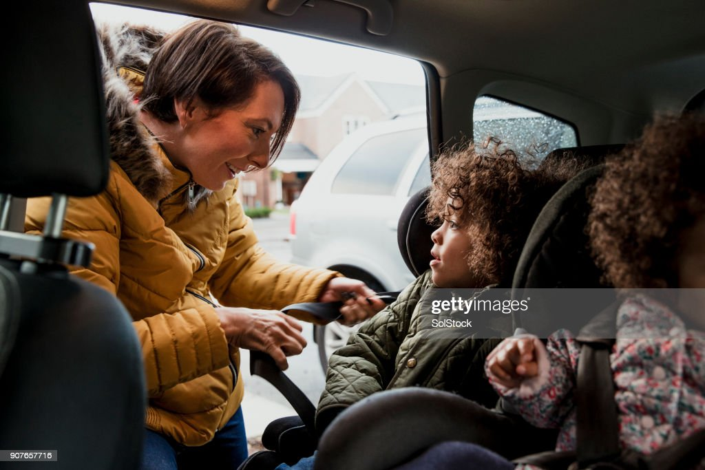 Putting Child Into Car Seat : Stock Photo