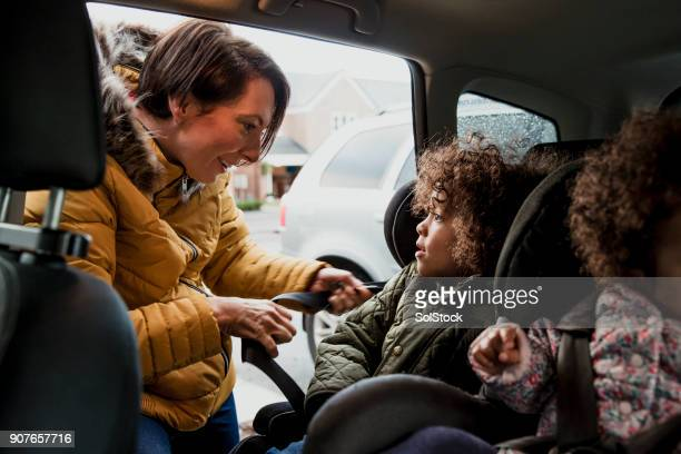 putting child into car seat - family inside car stock photos and pictures
