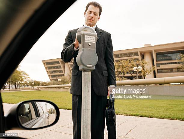 Putting coins into the parking meter