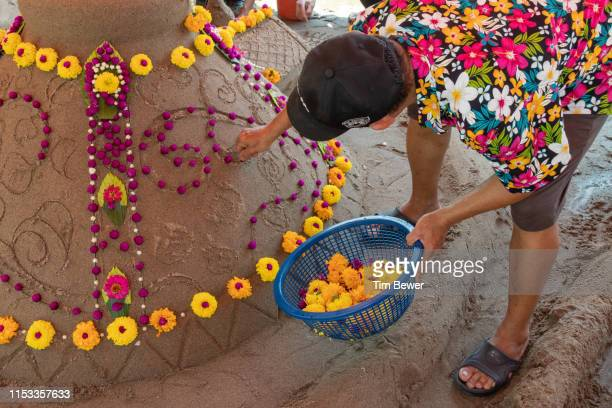 putting flowers in a sand stupa for the songkran festival. - tim bewer stock pictures, royalty-free photos & images