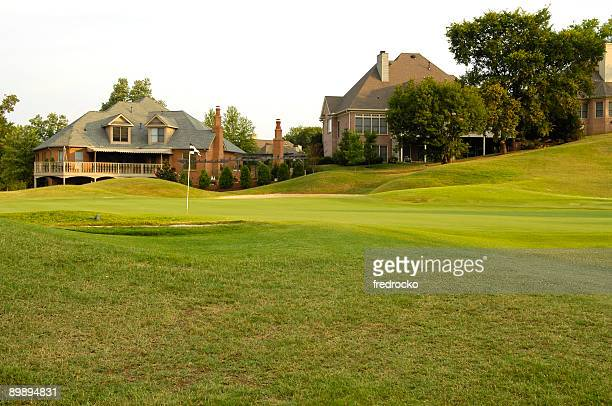 putting green on professional golf course near luxury homes - golf background stock photos and pictures