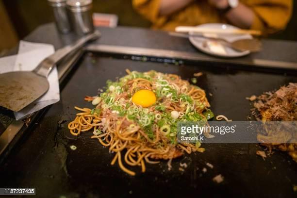 putting green onion and egg on yakisoba - okonomiyaki stock pictures, royalty-free photos & images