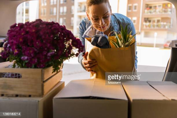 putting groceries in her car trunk - offloading stock pictures, royalty-free photos & images