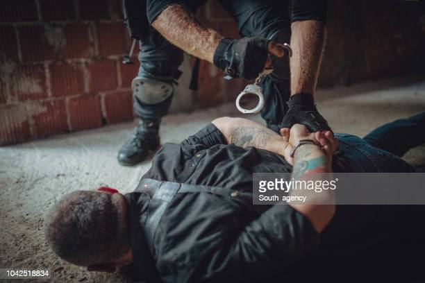 putting handcuffs on a criminal - shooting crime stock pictures, royalty-free photos & images