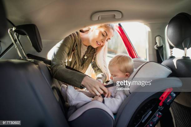 Putting Her Son in His Car Seat