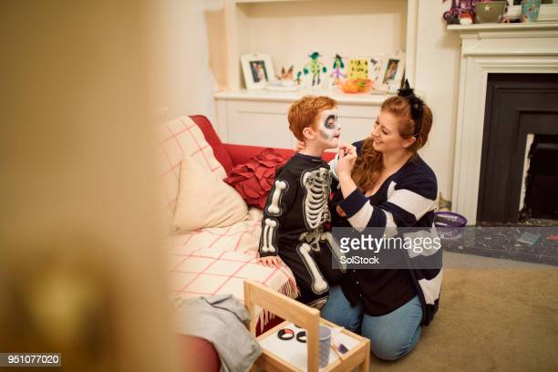 putting his makeup on for halloween - halloween zombie makeup stock photos and pictures