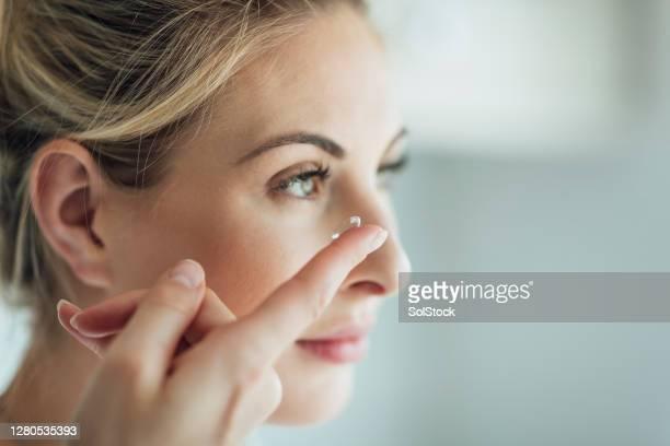 colocando uma lente de contato - lente - fotografias e filmes do acervo