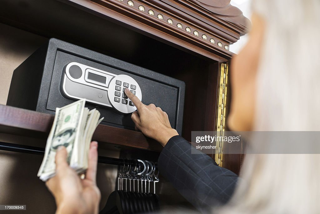 Putting money in safe. : Stock Photo