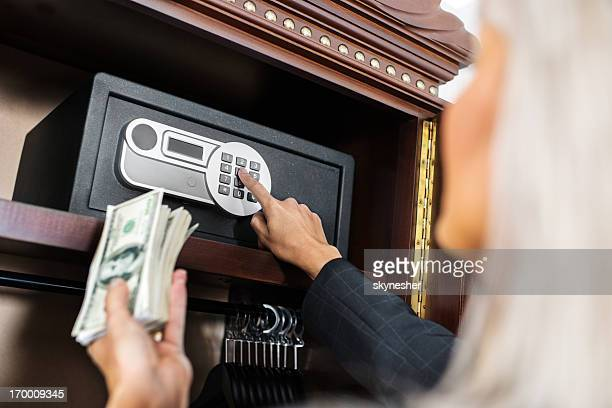 Putting money in safe.