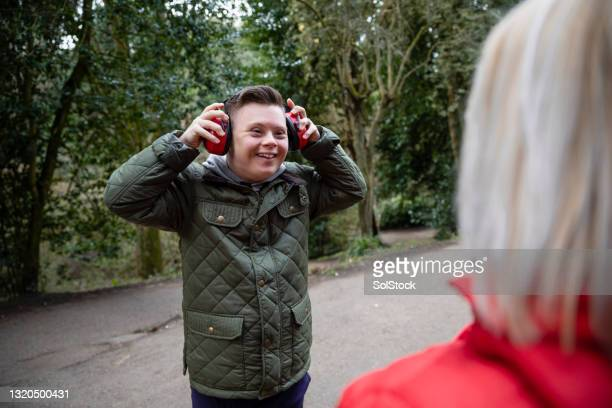 putting on protective ear defenders - support stock pictures, royalty-free photos & images