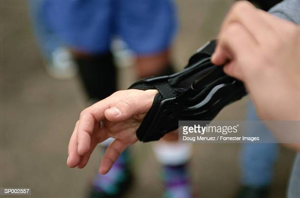 putting on wrist protector - brace stock pictures, royalty-free photos & images