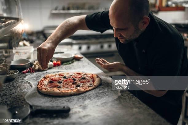 putting seasoning on pizza - fazer imagens e fotografias de stock