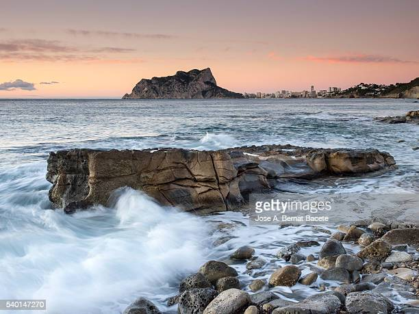 putting sun in a rock zone opposite to the nature reserve of ifach's crag, (peñon de ifach) - nature reserve stock pictures, royalty-free photos & images