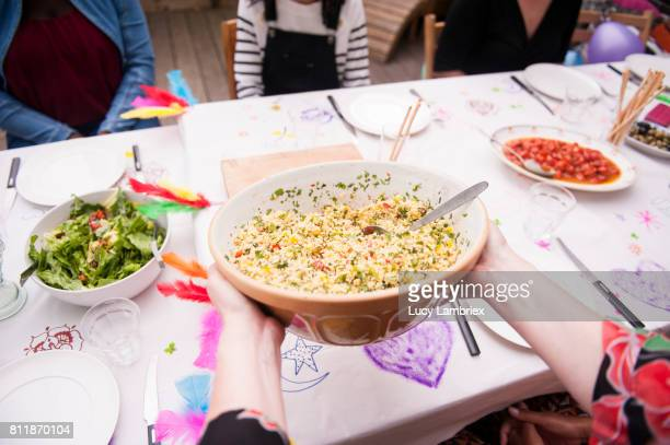 Putting the couscous salad on the table