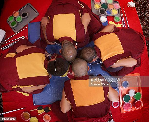 Putting their heads together to creat art and prayer Tibetan monks visiting Oak Grove School in Ojai Tuesday create a sand mandala meant to further...