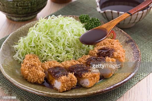 putting tonkatsu sauce on tonkatsu - tonkatsu photos et images de collection