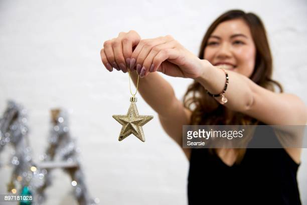 Putting up a star on  Christmas decorations