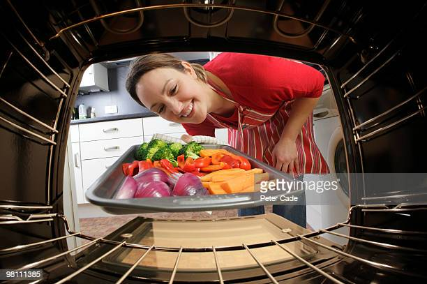putting vegetables into oven