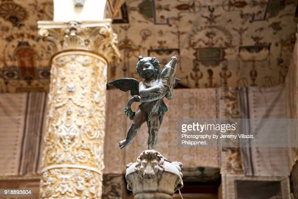 putto with dolphin, palazzo vecchio - cherub stock photos and pictures