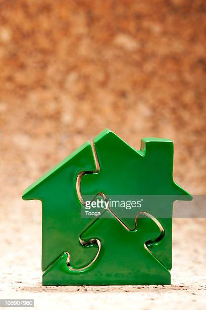 Puzzle of green house on cork background