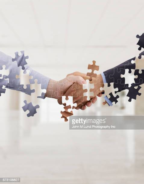 Puzzle pieces forming business people handshaking