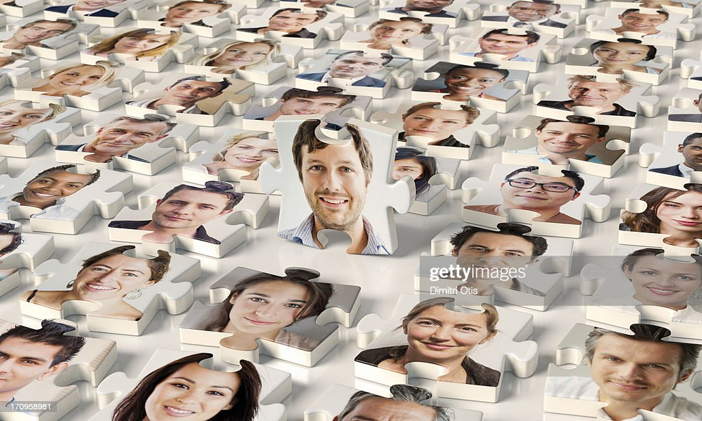 Puzzle pieces of faces, one standing up : Stock Photo