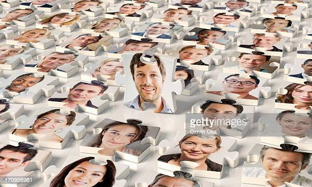 Puzzle pieces of faces, one standing up