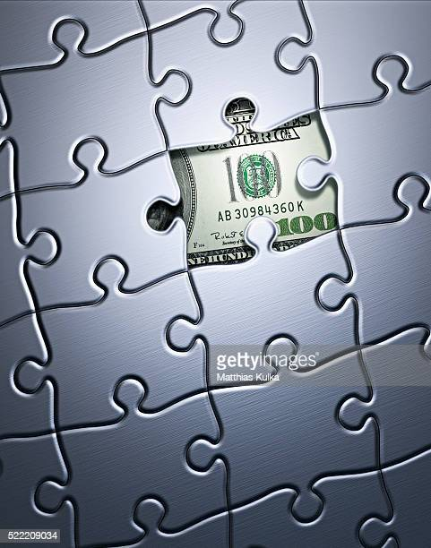 Puzzle with a one hundred dollar note in a missing piece