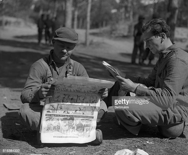 Pvc. John E. Blizzard, of Baltimore, MD. And Pvt. Rex Lowry, of Pendleton, Oregon, are reading the 'Funnies' at a rest camp set up amid comparative...