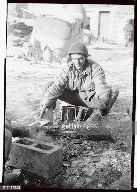 Pvt. Joseph Beaulieu, Haverhill, Mass., with the Third Army advancing on Houffalize, thaws out his frost bitten feet at a fire.