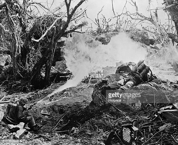 Pvt. Richard Klath, USMC, L, & Pfc. Wilfred Voegeli, USMC, throw a scorching inferno at high mighty defenses which block the way to Mt. Suribach on...