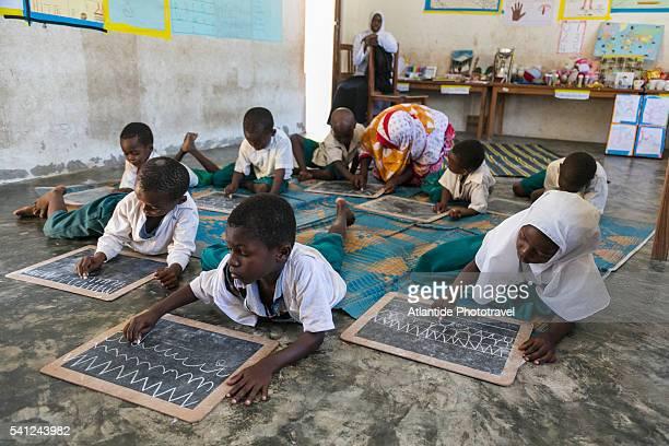 Pwani Mchangani, kindergarten, children drawing on chalkboards