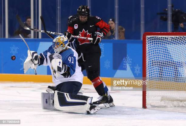 GANGNEUNG Pyeongchang FEBRUARY 13 Finland goaltender Noora Raty stops the puck with her blocker as Canada forward Blayre Turnbull looks for a rebound...