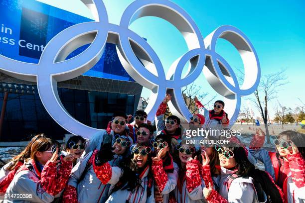 TOPSHOT Pyeongchang Olympic volunteers pose for a photo next next to the Olympics rings ahead of the Pyeongchang 2018 Winter Olympic Games in...