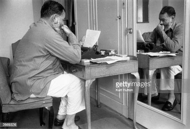 Pyjama clad author and journalist Ernest Miller Hemingway writes up copy for a report on World War II in Europe Hemingway is a war reporter and...