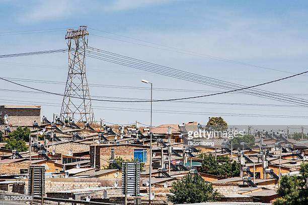 A pylon tower carries electrical power lines over residential shacks some equipped with solar power geysers on their roofs in the Alexandra township...