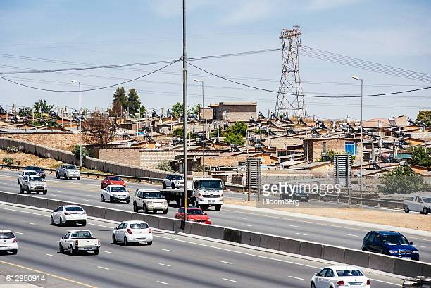 A pylon tower carries electrical power lines over residential shacks some equipped with solar power geysers on their roofs near a highway in the...