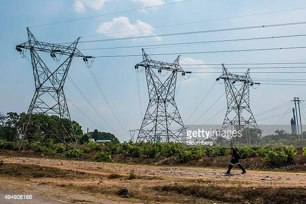 Pylons carry high voltage electricity power lines past a dirt road near the Mopani copper mine a Zambian unit of Glencore Plc in Kitwe Zambia on...