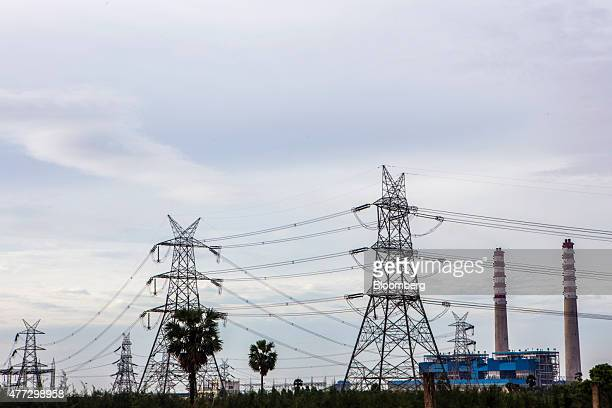 Pylons carrying power cables stand in front of the Simhapuri Energy Ltd power plant right in Thamminapatnam Andhra Pradesh India on Monday June 15...