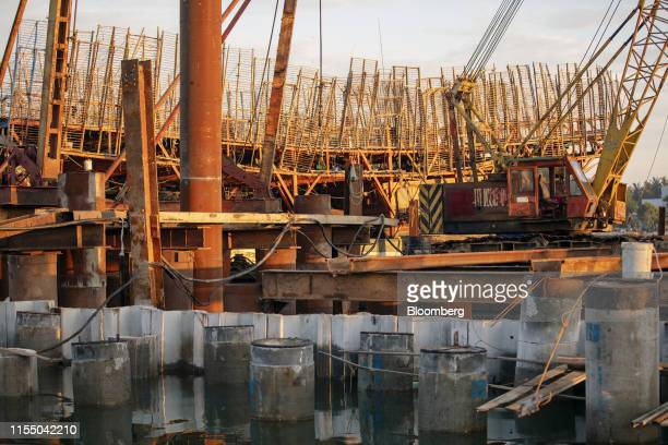 Pylons for a pier stand under construction in Tan Quang harbor in Quang Nam province Vietnam on Wednesday June 26 2019 Fishermen are on the front...