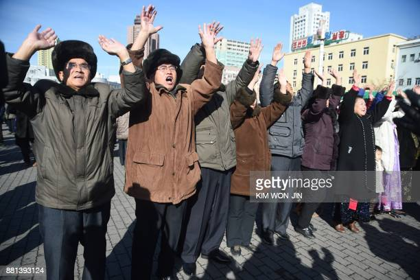 TOPSHOT Pyongyang residents react at the Pyongyang Railway Station after the news of the successful launch of the new intercontinental ballistic...
