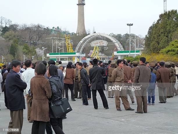Pyongyang residents wait outside a funfair in the centre of the North Korean capital Pyongyang in April 2011