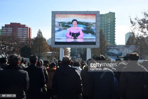 TOPSHOT Pyongyang residents watch a big screen near the Pyongyang Railway Station showing the news on the successful launch of the new...