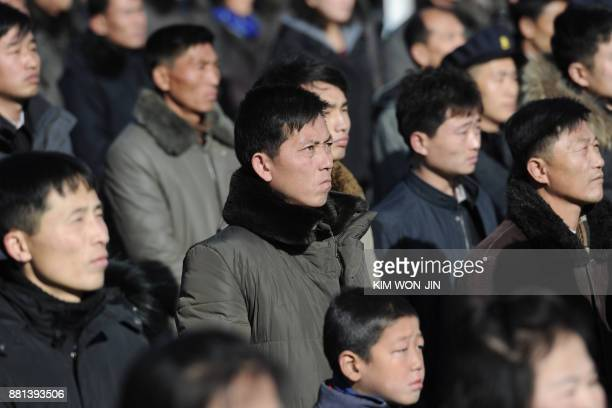Pyongyang residents watch a big screen near the Pyongyang Railway Station showing the news on the successful launch of the new intercontinental...
