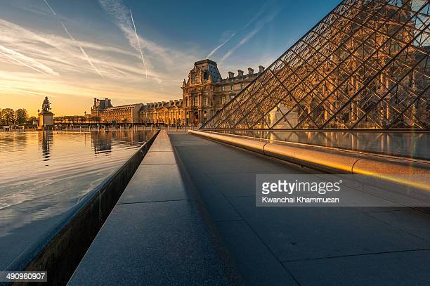 Pyramid and statue in the sunset at the Musee du Louvre.