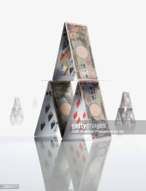 pyramid made of  yen and playing cards - japanese yen note stock photos and pictures