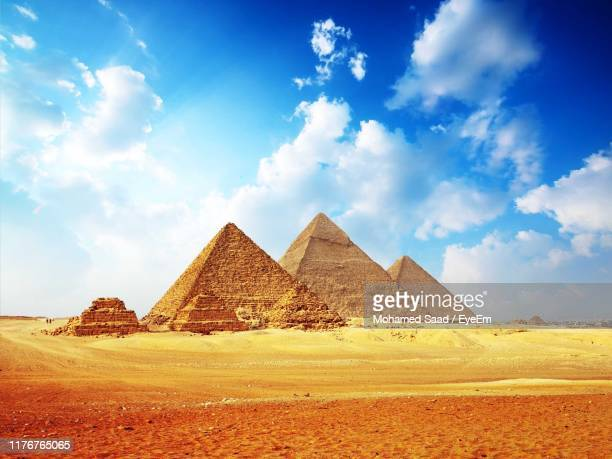 pyramids in desert against cloudy sky - エジプト ストックフォトと画像