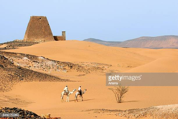 Pyramids of Meroe and two Nubian men dressed in thawbs riding dromedary camels in the Nubian desert of Sudan North Africa