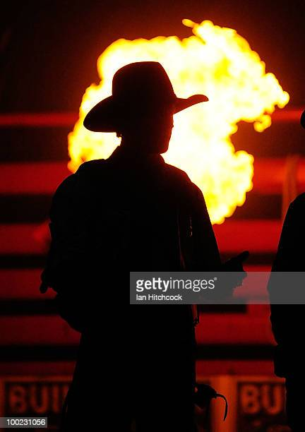 A pyrotechnic display goes off behind bull riders as they are introduced to the crowd before the start of the 2010 PBR Troy Dunn International at...